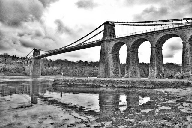 Creative black and white photograph of bridge with pale foreground colours